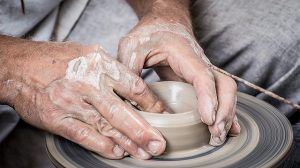 someone making a handmade clay pot